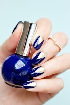 Beautiful v-shaped dark blue nail art design. The nails have a dark blue polish…