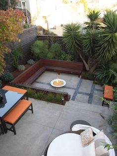 Gosh I love outdoor spaces! First, the unique trees and shrubs - landscaping becomes a design element! The built-in bench, fire pit, the orange cushion accents, and the pattern in the stone patio. Very understated, classy, and functional!