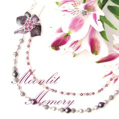 Purple enamel flower with amethyst crystals center on double-stand necklace of silver, mauve, pink, purple, and white Swarovski pearls and crystals. By MoonlitMemory on Etsy.