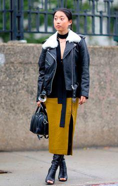 Street style look com jaqueta couro preta, skinny scarf, saia fenda e bota aberta.