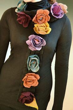 Lulu Scarf by Elizabeth Rubridge. Limited Edition. Wonderfully whimsical multi colored hand felted flower scarf made in merino wool. An open grid background is the base for a cascade of multi colored hand crafted poppy flowers. Glass bead centers catch the light for a special sparkle. Each piece is unique. Exact colors may vary, as shown in the images.