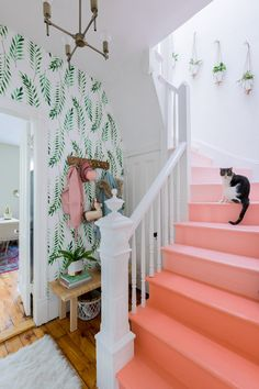 A ding hallway becomes a bright happy space with rainbow pink stairs and botanical wallpaper.