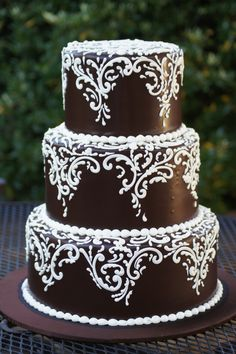Chocolate wedding cake with fancy white scrolling (white chocolate buttercream frosting desserts)