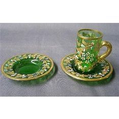 Enamelled miniature cup and two saucers
