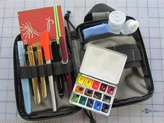 Sketching Kit by Maria Mercedes Trujillo. In a Maxpedition EDC Pocket Organiser- Left pocket: hand made journal 14x10 cm, with Hot Press 200g Artistico watercolor paper, large Pentel Aquash waterbrush, travel brushes No.10 and 6, mechanical pencil,  Pilot Parallel Pen 1.5 mm with J. Herbin Rouge Caroubier ink, Sailor Sapporo EF nib w/ Platinum Carbon Ink, Lamy Al-Star EF nib with Platinum Carbon Ink. Right pocket: W Bijou Box, microfiber sports towel, 2 small water containers, and eraser.