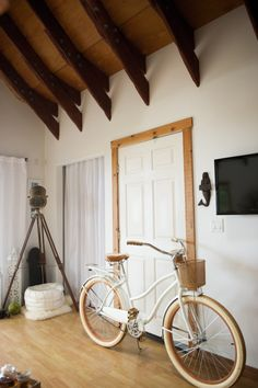 """""""This photo is a great shot of our awesome ceiling in the living area. I love the vaulted wooden beams and large industrial bolts securing them. My Maui beach cruiser is out and ready for a ride. I had it custom painted at a friend's auto body shop in a pearly white + gold flake. It was originally a light sky blue. Currently I am using the basket as a planter. My favorite morning routine includes hitting the streets of Haiku on this beauty in search of coffee and baked goods."""""""