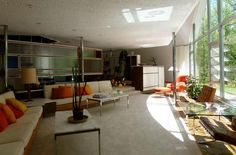 gorgeous mid century interior with large double height windows, orange and green interior with neutrals