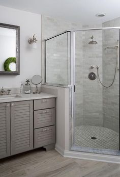 Amazing bathroom features a gray louvered vanity adorned with glass hardware placed under a Restoration Hardware Pharmacy Wall Mount Medicine Cabinet and 1920s factory Sconces atop a gray wood floor. A corner walk-in shower is filled with gray brick tiles and a white marble arabesque tile shower floor finished with a chrome and glass shower enclosure.
