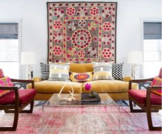 Bright living room with yellow velvet sofa, faded rug, acrylic coffee table, and wall-hung textile