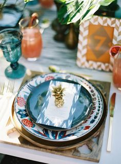 Mini gold pineapples. Table setting blues and oranges. Pretty.
