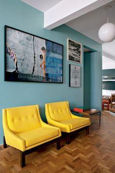 Poltronas amarelas em uma parede celeste acinzentado / mauricio arruda