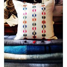 Embroidered souk sequin linen pillow sits atop a stack of Turkish rugs. #embroideredpillows #turkishrugs #linen