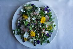 Edible flower salad with goat's cheese & tahini sauce. Place a handful of pea shoots on a plate, layer with a few slices of avocado, sprinkle withsome toasted seeds (sunflower, sesame, pumpkin). Scatter pieces of goat's cheese curd andsliced radish over the salad.  Make a dressing by whisking together a spoonful of tahini, the juice of 1/2 lime and a glugg of olive oil. Season with sea salt and pepper and drizzle over the salad. Garnish withedible flowers(violets or nasturtiums).