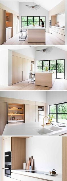 This modern and minimalist light wood and white kitchen features black accents like stools and window frames, a large central island, foldaway cabinet doors, and a pantry with hidden lighting.