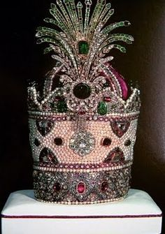 "The Kiani Crown was the traditional coronation crown in the Iranian Crown Jewels which was used during the Qajar dynasty (1796-1925). The crown itself is made of red velvet, on which thousands of gems were set. The Kiani Crown is highly decorated, possessing 1800 small pearls, many only 7 millimetres in diameter, stitched onto it. It has approximately 300 emeralds and 1800 rubies. The crown is 12.5"" tall."