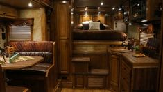 This Outlaw Conversions living quarters has beautiful Hickory Dark Brio wood, custom valances with inserts and fringe, unique leather, tin accent in the kitchen and so much more!