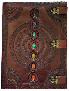 A massive tome with three latches to keep it closed and a line of 7 Chakra stones running down the front over the simple mandala centered on the cover. Embossing at the edge and on the rear cover may