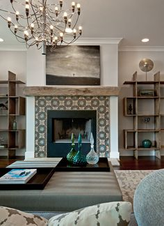 chandelier + tile fireplace + shelving units in living room by Buckingham Interiors