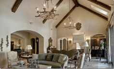 I love the scale of this room. The ceiling height is perfect.  Multiple sitting areas. Charming beams and chandeliers.
