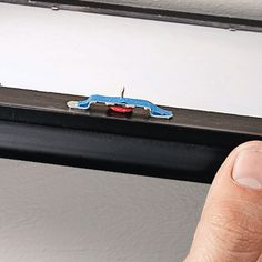 Easy picture hanging:  Tape a tack to the frame's hanger, as shown here. Just position the frame and push the tack into the wall to get a precise hole for your nail or picture hanging hardware.