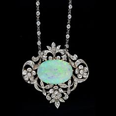 Edwardian Opal and Diamond Necklace, A lovely carat oval white opal cabochon is framed by garlands and floral motifs set with old mine cut diamonds in platinum over 18 karat yellow gold. This Edwardian gem is show on a platinum 18 inch diamond set chain. Opal Necklace, Opal Jewelry, Jewelry Box, Jewelry Accessories, Fine Jewelry, Jewelry Design, Pendant Necklace, Necklace Set, Jewellery Holder