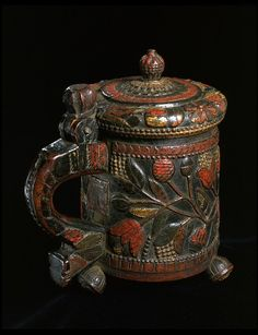 Tankard, carved and painted wood, Norway    This carved and painted tankard, with its hinged lid, is similar in form to metal tankards of the late 17th century. The carved version was probably made at least a century later and shows how strongly designs in the baroque style lasted in popular culture.