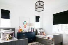 Contemporary boy's bedroom features a metal cage drum pendant illuminating a pair of gray shiplap trim twin beds with trundles dressed in black and orange plaid bedding flanking a black dresser as nightstand situated under windows dressed in black roman shades.