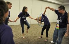 Students race to pass a hula hoop around each other while holding hands as they play.