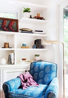 White styled bookshelves with a corner chair and brass lamp