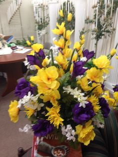 Silk cemetery vase using yellow gladiolus, yellow roses and mums, purple roses, purple lilies, and white gyp and freesia as fillers. May 2015 (Shook)