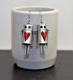Rock the town with these ROBOts! Oxidized sterling silver with red enamel hearts . Handcrafted with 3/8 diameter tubing and articulated appendages. These bots are on the larger side of your average earring but arent too heavy. Approximately 1 1/8 from head to toe and available in a variety