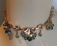 "This elegant necklace and earring set is inEXCELLENT CONDITION, and the draping necklace has a lovely scallop design setting encrusted with various sizes of sparkling emerald rhinestones. Thenecklace measures 13 ½"" L, and is closed by a sturdy gold-plated hook. 