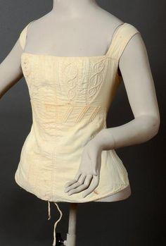 Corset, vers 1830, en sergé de coton crème doublée, entrelacs matelassés et piqués soulignant la poitrine, interstice cousu destiné à recevoir un busc; laçage dans le dos à 12 oeillets en os (taches sans gravité)