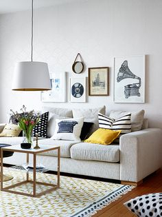 Love the neutral couch, splashes of color in accent pillows, low hanging light, coffee table and photo wall!