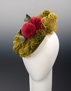 Wool cocktail hat with feather trim, by Dickerts, American, ca. 1940. Fruits and flowers have long been a popular millinery decoration. This whimsical example demonstrates how materials could be expertly manipulated by milliners to create shapes, here eye-popping magenta fruit or floral forms, creating a miniature garden vignette completely made of feathers.