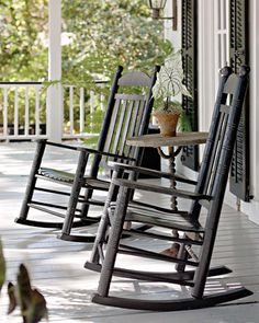 Vintage rocking chairs on the porch, paired with a stone-topped iron table from decorator Sim Harvey's Savannah shop, Arcanum.