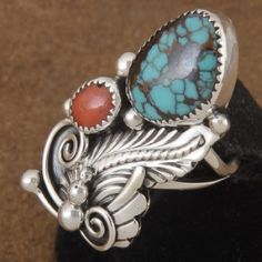 This genuine Nevada Number Eight Turquoise and Sterling Silver handcrafted Ring brings nature to your fingertips. Handmade in our shop by Navajo silversmith, Tom Ahasteen, this Native American ring will take your breath away! A spectacular, blue-green, Nevada turquoise stone with reddish-brown matrix is nested in a sawtooth Sterling bezel. Just above the Turquoise is a vivid, Red Coral cabochon surrounded in Sterling Silver. #168 #AllTribes
