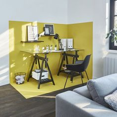 Une couleur stimulante pour le bureau. Dans ce salon épuré, l'espace bureau est délimité par la couleur jaune citron. Une démarcation visuelle au sol et au mur qui sépare de manière distincte le coin bureau du reste de