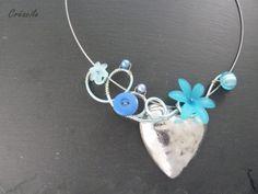 Collier en fil aluminium bleu glacé avec perles, bouton, fleurs et cœur en métal argenté. Le tour de cou est en fil câblé gris avec fermoir à vis.  Mélange des matières pour ce collier aux couleurs fraîches.  La légèreté des arabesques du fil contraste avec le cœur imposant en métal.  La combinaison des styles donne un côté à la fois moderne et romantique.