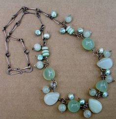 Lune Artisan Jewelry  |  The large smooth slightly irregular sea green stones are aqua agate, the teardrops and rounds are new jade, and the three mint green discs on either side are matte, opalescent glass discs from Happy Mango. The chain is handforged and all the sterling wire is lightly antiqued with Liver of Sulphur. Oh, and there are soft green freshwater pearls too.