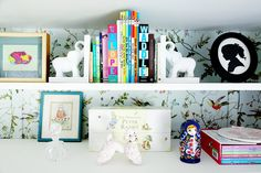 Wallpapered shelves +beautifully styled decor in this little girl's bookcase!