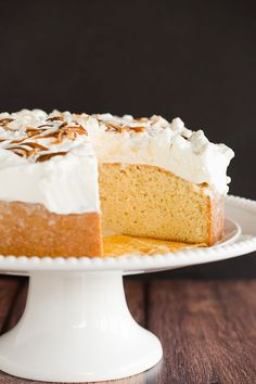 Caramel tres leches cake on a cake stand with a slice missing.