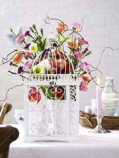 Easter table decor. Not so much the flower arr. but want one of these cages to twine with ivy or roses...
