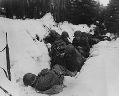 U.S. infantrymen of the 9th Infantry Regiment 2nd Infantry Division First U.S. Army crouch in a snow-filled ditch taking shelter from a German artillery barrage during the Battle of Heartbreak Crossroads in the Krinkelter woods on 14 December 1944.
