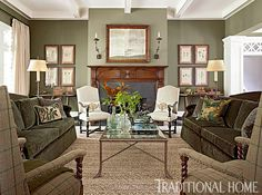 Sage green envelops the room in a cozy hue, while shapely green sofas face off in this space. - Photo: Erica Dines / Design: Barbara Westbrook