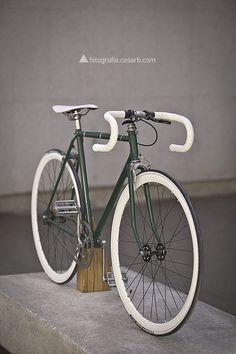 Bicycles: a gorgeous dark green fixie bike with white tyres and handlebars.