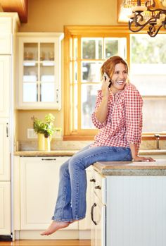 Beautiful woman sitting at home talking on the phone smiling.