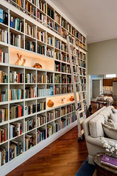 I love this look - full height fitted shelves with a proper library ladder. The spaces for displaying artwork are lovely