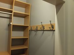More wall hooks for this his and hers set of small condo walk-in closets. Hooks for ties, belts and robes transform an unused wall into funtional storage space.