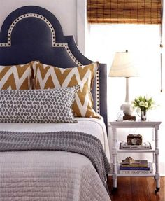 Navy headboard, white twill tape and nailhead trim, love the gold ikat pillows and bamboo nightstand on casters
